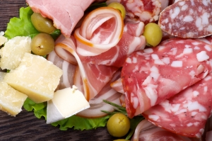 Arrangement of Delicatessen Cold Cuts with Smoked Ham, Various Sausages, Delicious Cheese and Green Olives closeup on Dark Wooden background