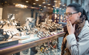 Astonished woman looking to showcase or shop window. Surprised shopping girl chooses jewelry in store