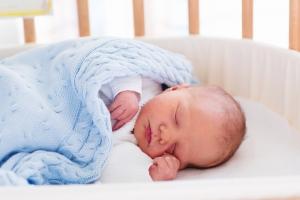 Bambino appena nato in stanza d'ospedale. Nuovo bambino nato in legno co-sleeper presepe. Infante addormentato nel letto culla. Cassetta di sicurezza co-dormire in una culla lato del letto. Ragazzino schiacciando un pisolino sotto coperta a maglia.
