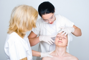 Two doctors women consulting a patient woman skin and the young doctor pointing and showing something on patient face to her colleague and preparing for botox treatment procedure