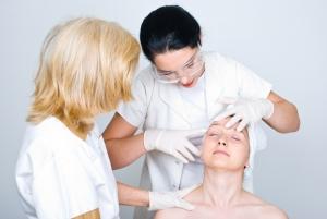 Due donne dei medici di consulenza una donna pelle del paziente e il giovane medico che indica e che mostra qualcosa sul viso del paziente al suo collega e la preparazione per la procedura trattamento di botox