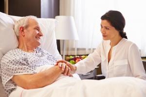 Donna medico parlando al paziente anziano maschio nel letto di ospedale