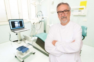 Senior dentist standing in his dental operatory