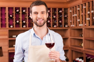 enologo fiducioso. Fiducioso giovane uomo in grembiule in possesso di vetro con il vino rosso, mentre in piedi in cantina