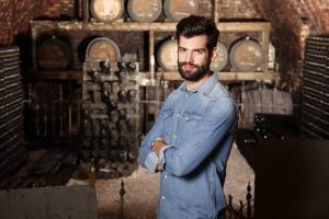 Retrato de joven enólogo de pie en su bodega de vino delante de cañón y mirando a la cámara. Pequeños negocios.